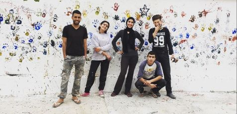 A volunteer and her students paint a wall in Moulay Idriss.
